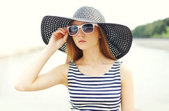 Beautiful young woman wearing a striped dress, black straw hat and sunglasses Stock Photos