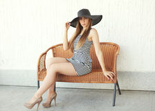 Beautiful young woman wearing a striped dress and straw hat Stock Photography