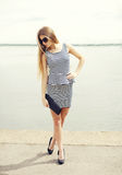 Beautiful young woman wearing a striped dress, sunglasses and handbag clutch Royalty Free Stock Photo