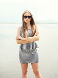 Beautiful young woman wearing a striped dress, sunglasses Royalty Free Stock Photography