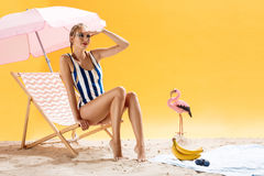 Beautiful young woman wearing striped swimsuit. Isolated over yellow background. Beautiful young woman wearing striped swimsuit sitting on cool beach chair royalty free stock images