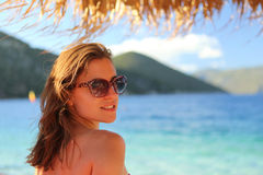 Beautiful young woman wearing sunglasses and smiling on the beach. Beautiful young woman under an umbrella at the beach Royalty Free Stock Photography