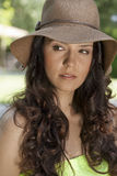 Beautiful young woman wearing sunhat looking away in park Stock Photo