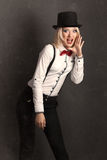 Beautiful young woman wearing tophat, bow-tie and braces against Royalty Free Stock Photos