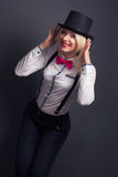 Beautiful young woman wearing tophat, bow-tie and braces against Stock Photo