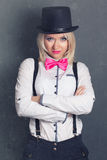 Beautiful young woman wearing tophat, bow-tie and braces against Royalty Free Stock Images