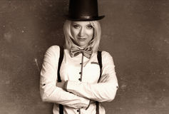 Beautiful young woman wearing tophat, bow-tie and braces against Stock Photography