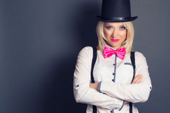 Beautiful young woman wearing tophat, bow-tie and braces against Stock Image