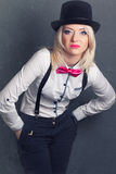 Beautiful young woman wearing tophat, bow-tie and braces against Stock Photos