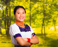 Beautiful young woman wearing traditional andean blouse with necklace, standing posing for camera, arms crossed smiling Stock Image