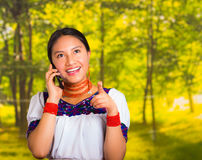 Beautiful young woman wearing traditional andean blouse with necklace, standing posing for camera, holding mobile phone Stock Photos