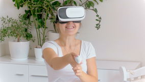 Beautiful young woman wearing virtual reality headset playing in 3d game and using joystick. Footage shot at 4k stock video footage