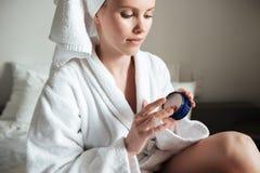 Beautiful young woman wearing white bathrobe applying body lotion Royalty Free Stock Photography