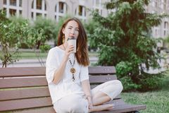 Dreaming woman sitting with paper cup of coffee in summer park. stock images
