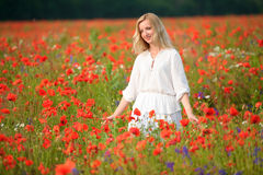 Beautiful young woman wearing white dress walking thru a bloomin. The beautiful young woman wearing white dress walking thru a blooming summer field Stock Photos