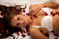 Beautiful young woman wearing white lingerie lying in bed of ros Royalty Free Stock Photo
