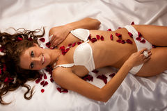 Beautiful young woman wearing white lingerie lying in bed of ros Stock Images