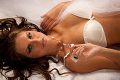 Beautiful young woman wearing white lingerie lying in bed on sil Royalty Free Stock Photos