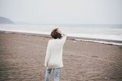 Beautiful young woman wearing white sweater and blue jeans walking on a lonely beach Stock Image
