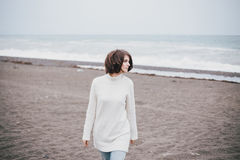 Beautiful young woman wearing white sweater and blue jeans walking on a lonely beach Stock Images