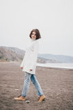 Beautiful young woman wearing white sweater and blue jeans walking on a lonely beach Royalty Free Stock Photography