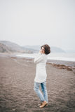 Beautiful young woman wearing white sweater and blue jeans walking on a lonely beach Royalty Free Stock Images