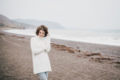 Beautiful young woman wearing white sweater and blue jeans walking on a lonely beach Stock Photography