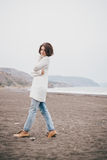 Beautiful young woman wearing white sweater and blue jeans walking on a lonely beach Stock Photos