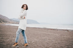 Beautiful young woman wearing white sweater and blue jeans walking on a lonely beach Royalty Free Stock Photos