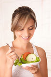 Beautiful young woman wearing a white t-shirt and holding in her hand a healthy salad and using a fork.  Royalty Free Stock Photography