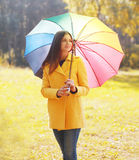 Beautiful young woman wearing a yellow coat with umbrella Stock Images
