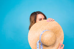 Beautiful young woman wears in summer dress and straw hat is laughing on blue background with copy space Royalty Free Stock Photography