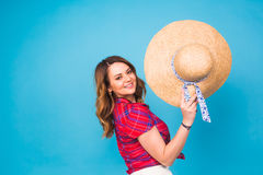 Beautiful young woman wears in summer dress and straw hat is laughing on blue background with copy space Stock Photos