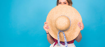 Beautiful young woman wears in summer dress and straw hat is laughing on blue background with copy space Royalty Free Stock Photo