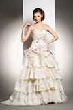 The beautiful young woman in a wedding dress. The beautiful young woman posing in a wedding dress over grey backround Royalty Free Stock Images