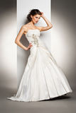 The beautiful young woman in a wedding dress. The beautiful young woman posing in a wedding dress over grey backround Stock Photo