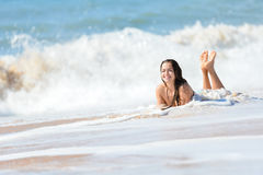 Beautiful young woman with wet hair lying on ocean Stock Photography