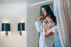 Beautiful young woman in white bathrobe  bedroom at home Royalty Free Stock Image
