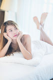 Beautiful young woman in white bathrobe in bedroom at home Stock Photos
