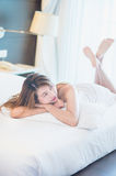 Beautiful young woman in white bathrobe in bedroom at home Royalty Free Stock Photo