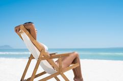Woman sunbathing at beach. Beautiful young woman in white bikini lying on a deckchair while sunbathing. Woman relaxing on a deck chair at the seaside. Tanned Royalty Free Stock Image