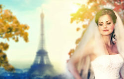 Beautiful young woman in white bride dress with silhouette of Eiffel tower in Paris Royalty Free Stock Photography