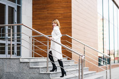 Beautiful young woman in white coat. Climbing stairs in business building Stock Photography