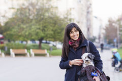 Beautiful young woman with white dog in carry bag Stock Images