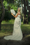 Beautiful young woman in white dress. In forest Stock Photo