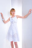 Beautiful young woman in a white dress. The girl relies both hands on the wall. Blonde Stock Photo