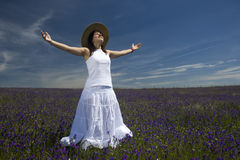 Beautiful young woman in white dress with arms wide open Stock Photo