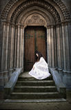 Beautiful young woman in white dress at church stairs. Book cover. Royalty Free Stock Photos