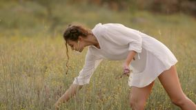 Natural beauty girl gathering flowers outdoor in freedom enjoyment concept. stock video footage