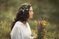 Natural beauty girl with bouquet of flowers outdoor in freedom enjoyment concept. Portrait photo. Beautiful young woman in white dress collecting wild flowers at royalty free stock image